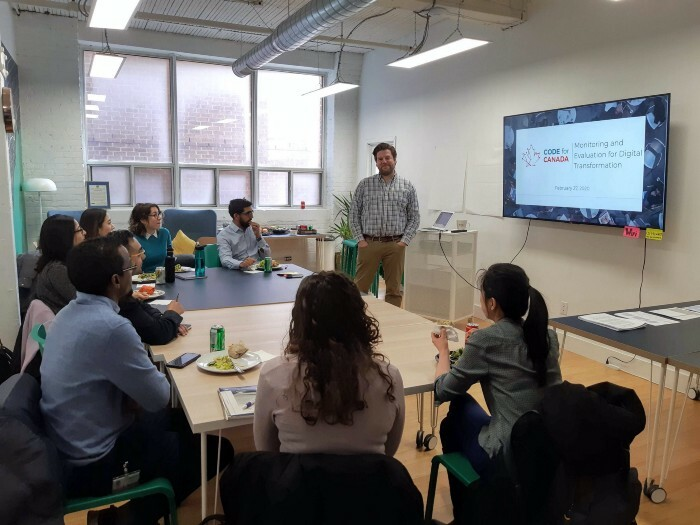 Merlin Chatwin (standing, center) leads a workshop on monitoring and evaluation for members of Civic Hall Toronto on February 27, 2020.